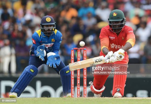 Zimbabwe's cricketer Solomon Mire is watched by Sri Lankan wicketkeeper Niroshan Dikwella as he plays a shot during the fourth oneday international...