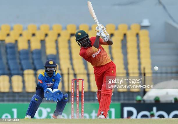 Zimbabwe's cricketer Solomon Mire is watched by Sri Lankan wicketkeeper Niroshan Dikwella as he plays a shot during the fifth oneday international...