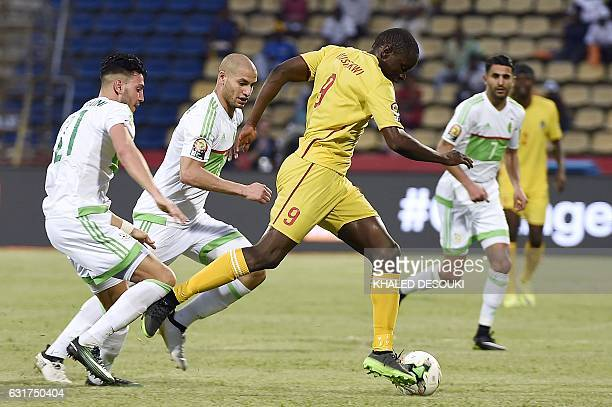 Zimbabwe's forward Nyasha Mushweki advances with the ball past Algeria's defender Rami Bensebaini and Algeria's midfielder Adlene Guedioura during...