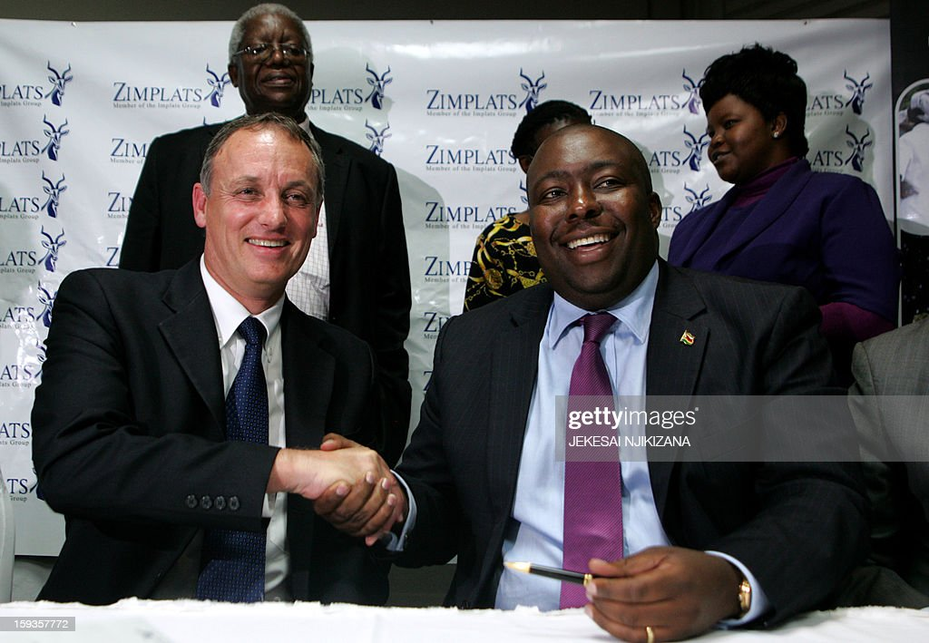 Zimbabwe's Indigenisation minister Saviour Kasukuwere (R) and the Chief Executive of platinum mining giant Implats Terence Goodlace, shake hands on January 11, 2013 after a ceremony in Harare. Impala Platinum, the world's number two producer of platinum on January 11 sealed a deal to sell a 51-percent stake in its Zimbabwean unit Zimplats under a state-imposed black empowerment scheme. AFP PHOTO / Jekesai Njikizana