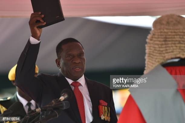 Zimbabwe's new interim President Emmerson Mnangagwa takes the oath of office before Chief judge of the Supreme Court Luke Malaba as he is officially...