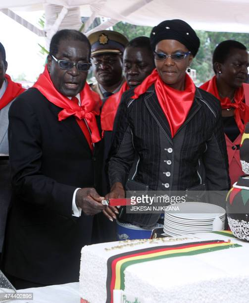 Zimbabwe's President Robert Mugabe cuts his birthday cake next to his wife Grace during celebrations marking his 90th birthday in Marondera on...