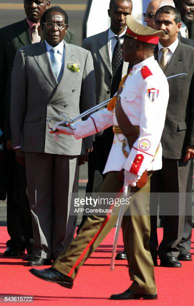 Zimbabwe's President Robert Mugabe is welcomed by Cuban Justice minister Roberto Diaz Sotolongo at the Jose Marti Airport in Havana 13 September 2006...