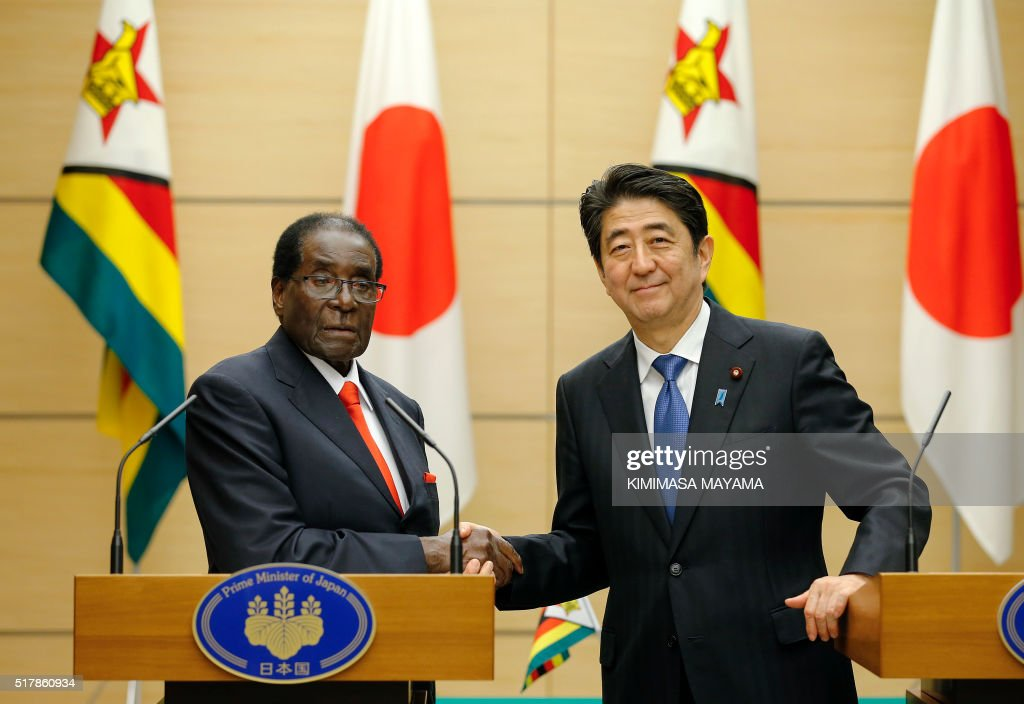 Zimbabwe's President Robert Mugabe (L) shakes hands with Japan's Prime Minister Shinzo Abe following their joint press conference at the latter's official residence in Tokyo on March 28, 2016.Mugabe arrived in Japan on March 27 for a five-day official working visit. / AFP / POOL / Kimimasa Mayama