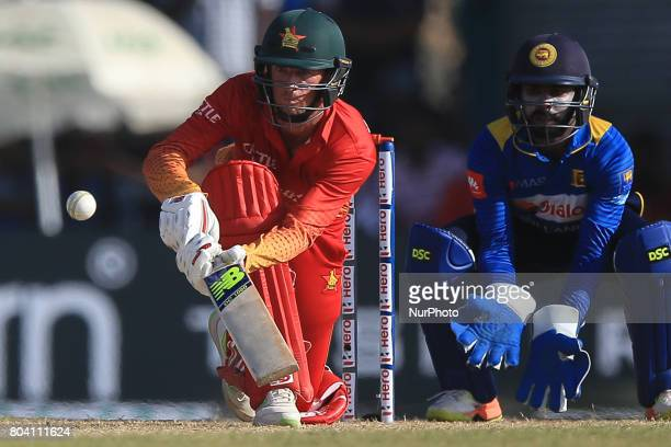 Zimbabwe's Sean Williams plays a shot as Sri Lanka's Niroshan Dickwella looks on during the 1st ODI cricket match at the Galle International cricket...
