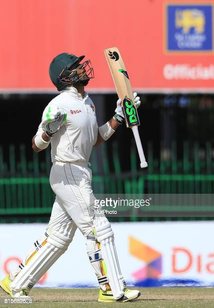 Zimbabwe's Sikandar Raza looks up to the sky and reacts after scoring fifty runs during the third day's play of the only test cricket match between...