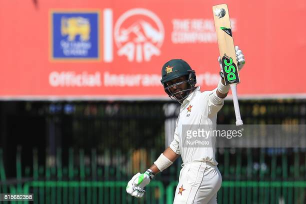 Zimbabwe's Sikandar Raza raises his ba after scoring fifty runs during the third day's play of the only test cricket match between Sri Lanka and...