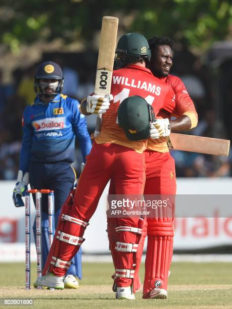 Zimbabwe's Solomon Mire celebrates after scoring his century with teammates Sean Williams during the first oneday international cricket match between...