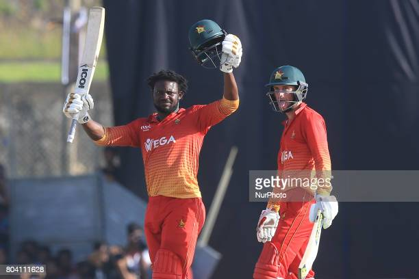 Zimbabwe's Solomon Mire celebrates his maiden century in ODI cricket as his partner Sean Williams looks on during the 1st ODI cricket match at the...
