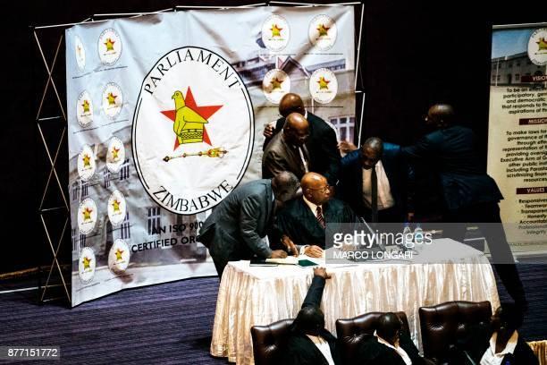 TOPSHOT Zimbabwe's speaker of parliament Jacob Mudenda receives the news that president Robert Mugabe resigned on November 21 2017 at the parliament...
