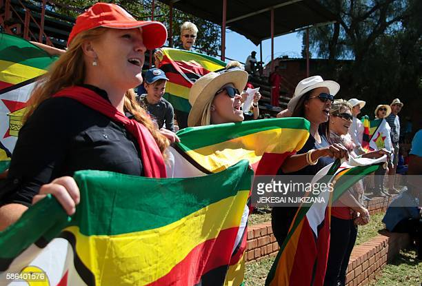 Zimbabwe's supporters sing the national anthem during the first day of the second test in a series of two matches where New Zealand leads hosts...