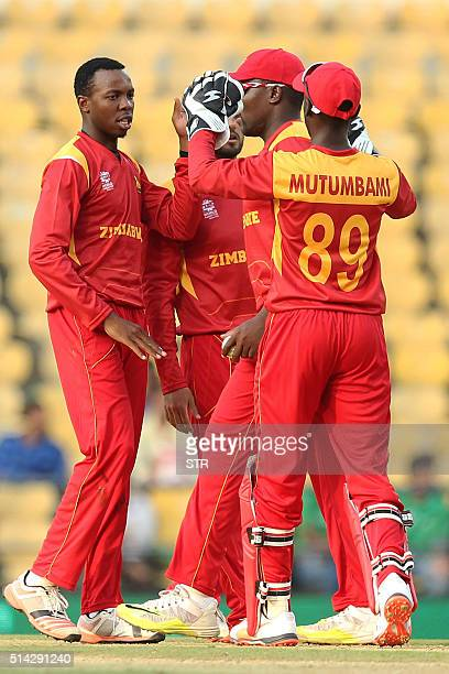 Zimbabwe's Wellington Masakadzacelebrates with teammates after taking the wicket of unseen Hong Kong batsman Babar Hayat during the opening match of...