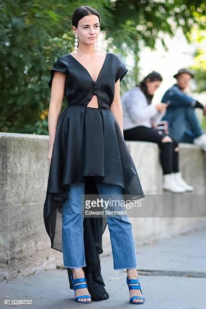 Zina Charkoplia is wearing a black dress blue denim jeans blue shoes and a clutch outside the Rochas show at the Palais de Tokyo during Paris Fashion...