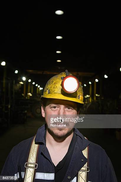 zinc miner in heavy vehicle repair shop, portrait