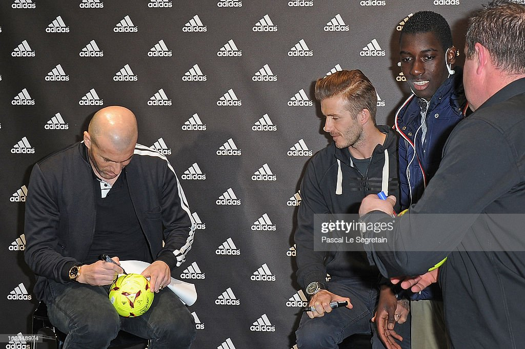 Zinedine Zidane and David Beckham meet with a fan as they attend an autograph session at adidas Performance Store Champs-Elysees on February 28, 2013 in Paris, France.