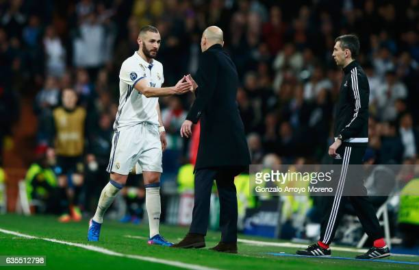Zinedine Zidane head coach of Real Madrid shakes hands with Karim Benzema of Real Madrid during the UEFA Champions League Round of 16 first leg match...