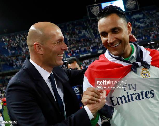 Zinedine Zidane Manager of Real Madrid celebrates with Danilo of Real Madrid after being crowned champions following the La Liga match between Malaga...