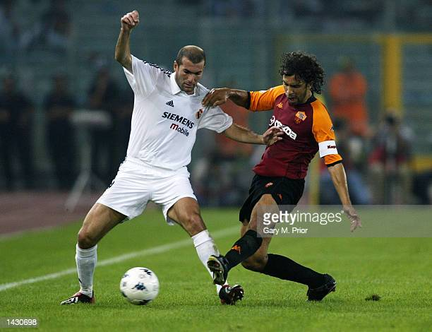 Zinedine Zidane of Real Madrid is challenged by Damiano Tommasi of Roma during the UEFA Champions League First Phase Group C match between AS Roma...
