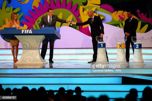 Zinedine Zidane passes one of the draw balls to FIFA Secretary General Jerome Valcke during the Final Draw for the 2014 FIFA World Cup Brazil at...