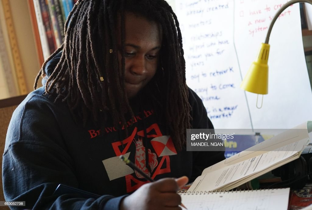 Zion, 17, who is homeschooled by his mother Monica Utsey, works at a table at home in Washington, DC on February 24, 2017. /