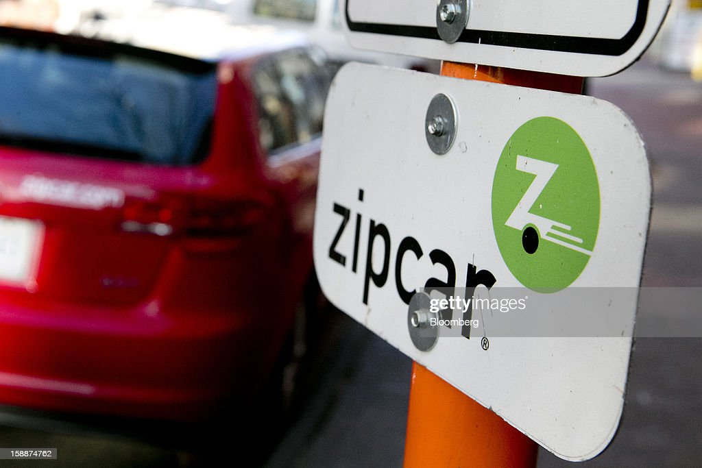 Zipcar Inc. signage stands next to vehicles parked in the company's spaces in Washington, D.C., U.S., on Wednesday, Jan. 2, 2013. Avis Budget Group Inc., once a skeptic about car sharing services, agreed to buy short-term rental pioneer Zipcar for $491 million, signaling a shift in the industry to embracing drivers who don't want to own cars. Photographer: Andrew Harrer/Bloomberg via Getty Images