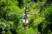 A girl is photographed sliding down an aerial steel cable (zipwire) at high speed in the rainforest in Costa Rica.