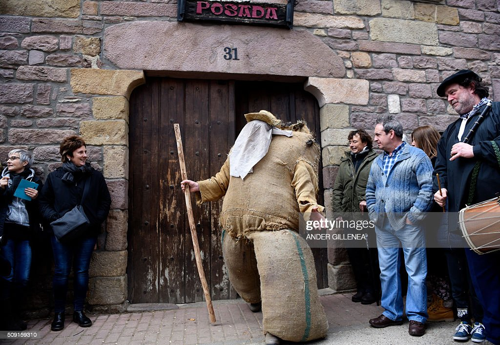 Ziripot, a man dressed with a straw costume, leaves a house to walk the streets during the ancient carnival of Lantz, in the northern Spanish Navarre village of Lantz, on February 9, 2016. / AFP / ANDER GILLENEA