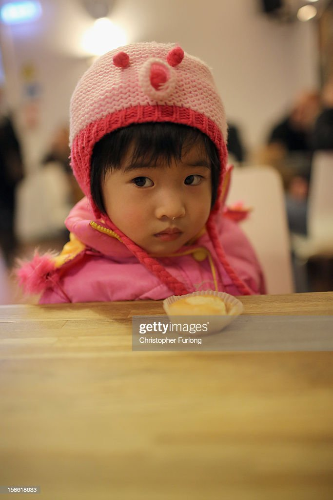 Ziyi Fang, aged 2, is given a cupcake as she waits with her mother to collect essential Christmas food at Liverpool Central Foodbank on December 21, 2012 in Liverpool, England. With Christmas only days away, volunteers at the Central Liverpool Foodbank at the Frontline Trust, have seen one of their busiest days of the year as they give out free food for the needy. The centre has been giving out festive treats as well as its normal food donation - feeding over 1000 individuals in its first year, including over 300 children.