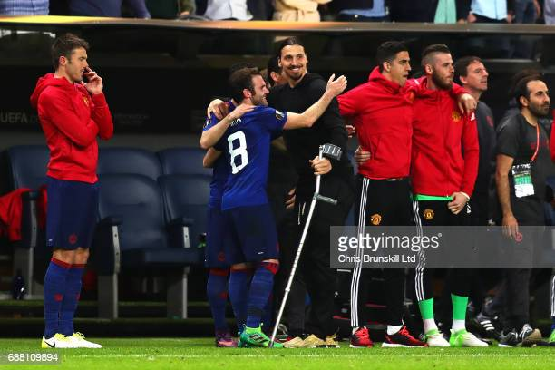 Zlatan Ibrahimovic of Manchester United celebrates with teammate Juan Mata on the touchline during the UEFA Europa League Final match between Ajax...