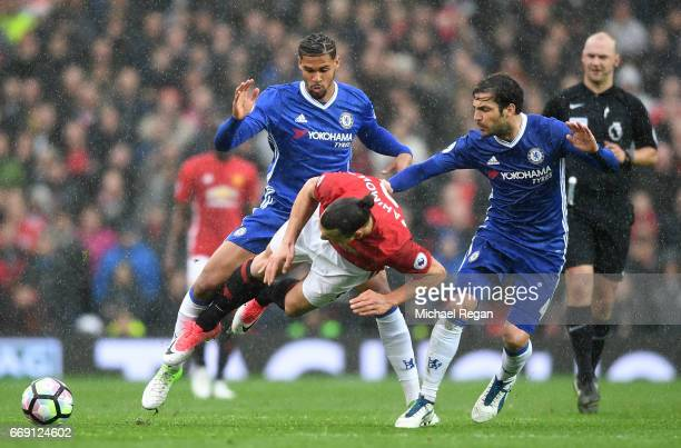 Zlatan Ibrahimovic of Manchester United is fouled by Cesc Fabregas of Chelsea and Ruben LoftusCheek of Chelsea during the Premier League match...
