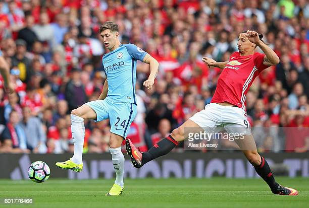 Zlatan Ibrahimovic of Manchester United is tackled by John Stones of Manchester City during the Premier League match between Manchester United and...