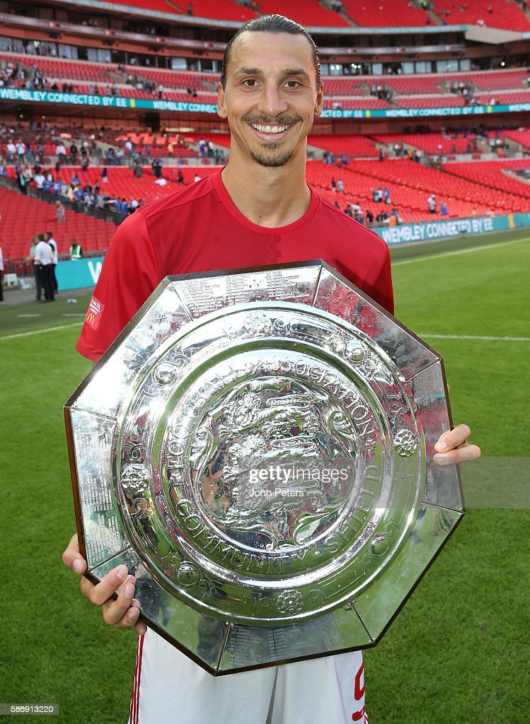 Zlatan Ibrahimovic of Manchester United poses with the Community Shield trophy in the dressing room after the FA Community Shield match between...