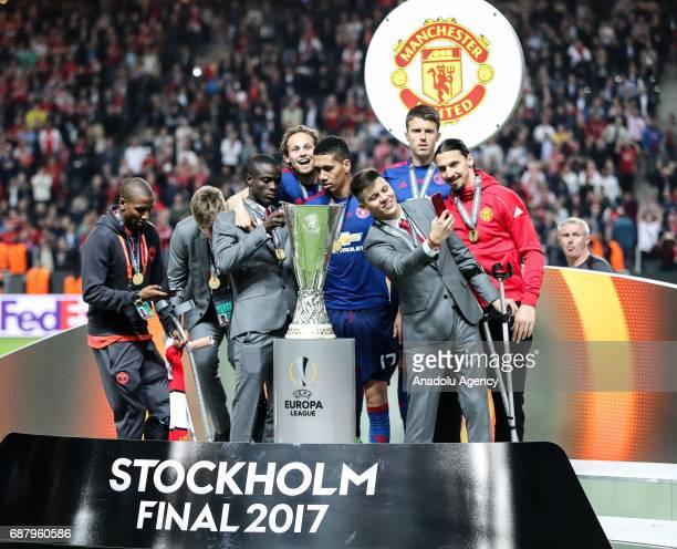 Zlatan Ibrahimovic of Manchester United takes a photo near the trophy as he celebrates after the UEFA Europa League Final match between Ajax and...