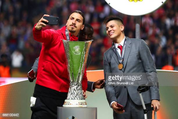 Zlatan Ibrahimovic of Manchester United takes a selfie with the trophy as teammate Marcus Rojo looks on following the UEFA Europa League Final match...
