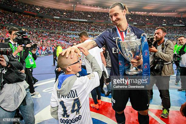 Zlatan Ibrahimovic of Paris SaintGermain celebrates with a fan the victory of the French Cup Final between AJ Auxerre and Paris SaintGermain at Stade...