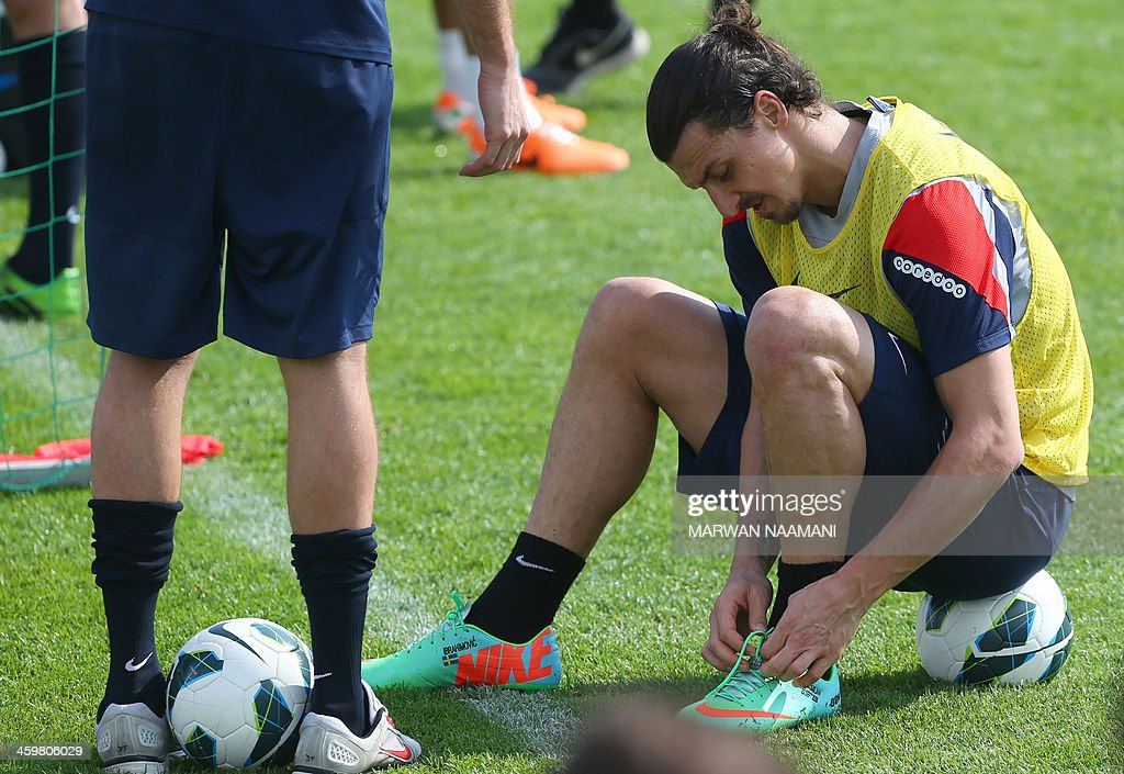 Zlatan Ibrahimovic of Paris Saint-Germain team buckles his sports shoes during a training session at the Aspire Academy of Sports Excellence in the Qatari capital Doha on December 31, 2013. AFP PHOTO/MARWAN NAAMANI