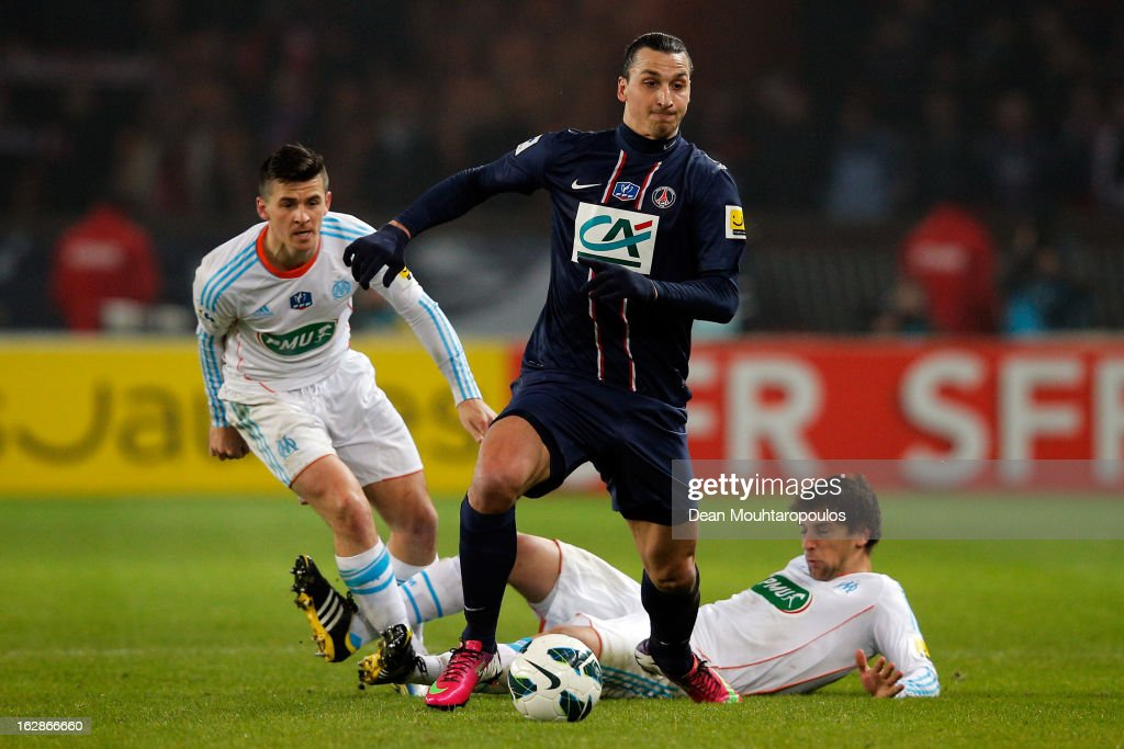 <a gi-track='captionPersonalityLinkClicked' href=/galleries/search?phrase=Zlatan+Ibrahimovic&family=editorial&specificpeople=206139 ng-click='$event.stopPropagation()'>Zlatan Ibrahimovic</a> of PSG beats Michel Lucas Mendes and <a gi-track='captionPersonalityLinkClicked' href=/galleries/search?phrase=Joey+Barton&family=editorial&specificpeople=211284 ng-click='$event.stopPropagation()'>Joey Barton</a> of Marseille during the French Cup match between Paris Saint-Germain FC and Marseille Olympic OM at Parc des Princes on February 27, 2013 in Paris, France.