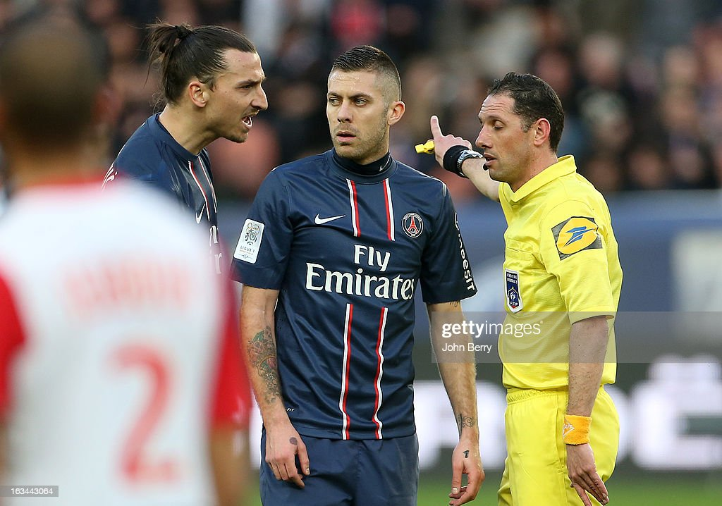 Zlatan Ibrahimovic of PSG (L) disagrees with referee Mikael Lesage and shows it while Jeremy Menez looks on during the french Ligue 1 match between Paris Saint-Germain FC and AS Nancy-Lorraine ASNL at the Parc des Princes stadium on March 9, 2013 in Paris, France.