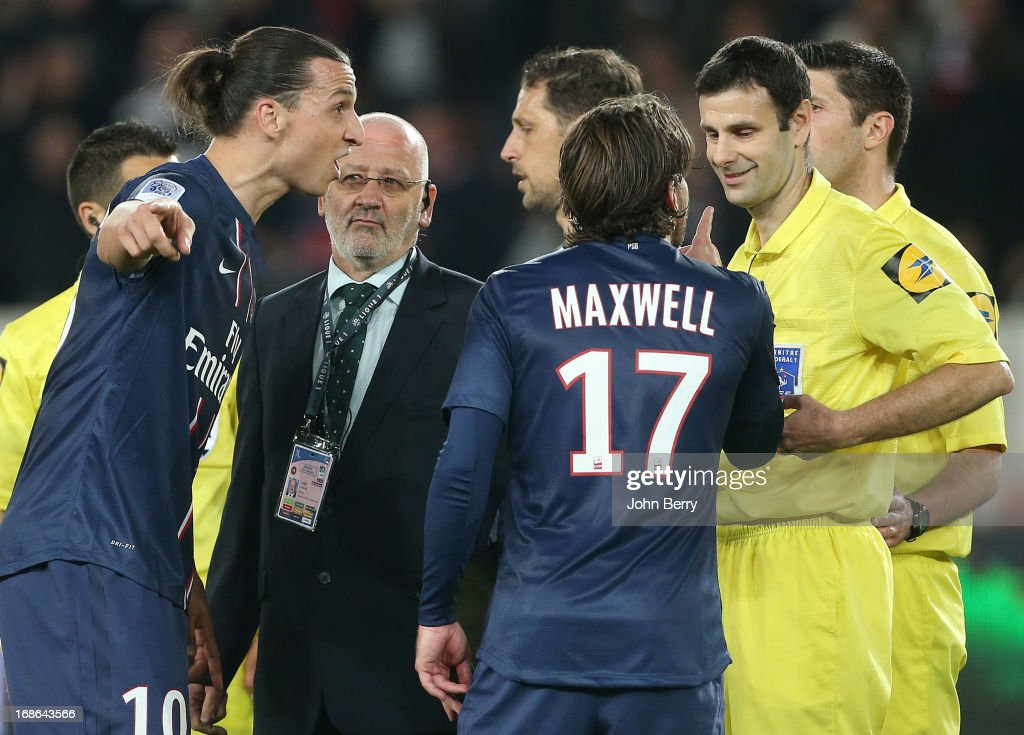 Zlatan Ibrahimovic of PSG receives a yellow card for contestation from referee Alexandre Castro while Maxwell Scherrer comes to his defense at the end of the Ligue 1 match between Paris Saint-Germain FC and Valenciennes FC at the Parc des Princes stadium on May 5, 2013 in Paris, France.