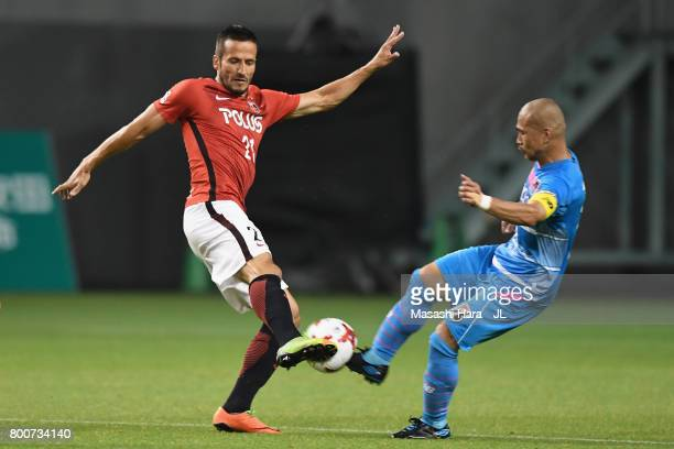 Zlatan Ljubijankic of Urawa Red Diamonds and Yutaka Yoshida of Sagan Tosu compete for the ball during the JLeague J1 match between Sagan Tosu and...