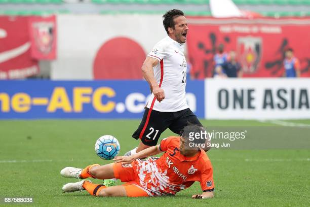 Zlatan Ljubijankic of Urawa Red Diamonds competes for the ball with Kweon HanJin of Jeju United FC during the AFC Champions League Round of 16 match...