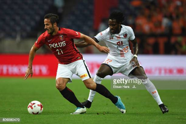 Zlatan Ljubijankic of Urawa Red Diamonds controls the ball under pressure of Caue of Omiya Ardija during the JLeague J1 match between Urawa Red...