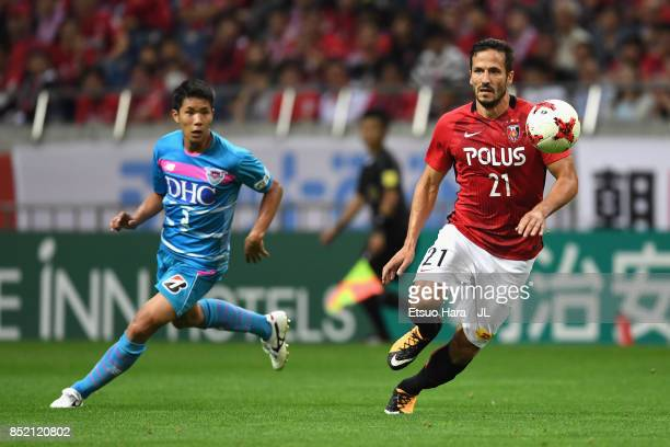 Zlatan Ljubijankic of Urawa Red Diamonds controls the ball under pressure of Hiromu Mitsumaru of Sagan Tosu during the JLeague J1 match between Urawa...
