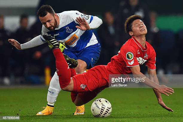 Zlatko Janjic of Duisburg challenges Kazuki Nagasawa of Koeln during the DFB Cup second round match between MSV Duisburg and 1 FC Koeln at...
