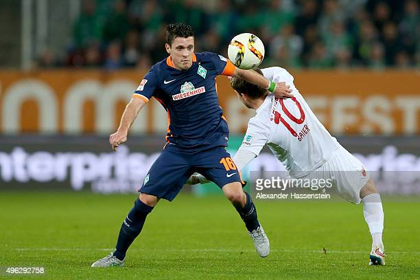 Zlatko Junuzovic of Bremen battles for the ball with Daniel Baier of Augsburg during the Bundesliga match between FC Augsburg and SV Werder Bremen at...