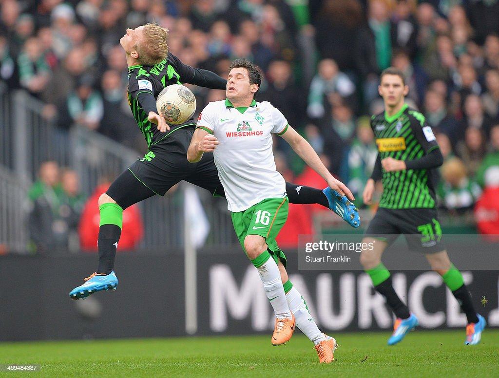 Zlatko Junuzovic of Bremen is challenged by Oscar Wendt of Gladbach during the Bundesliga match between Werder Bremen and Borussia Moenchengladbach at Weserstadion on February 15, 2014 in Bremen, Germany.