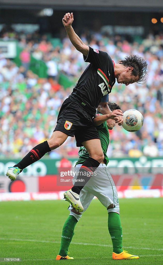 Zlatko Junuzovic of Bremen is challenged by Paul Verhaeghof Augsburg during the Bundesliga match between Werder Bremen and FC Augsburg at Weserstadion on August 17, 2013 in Bremen, Germany.