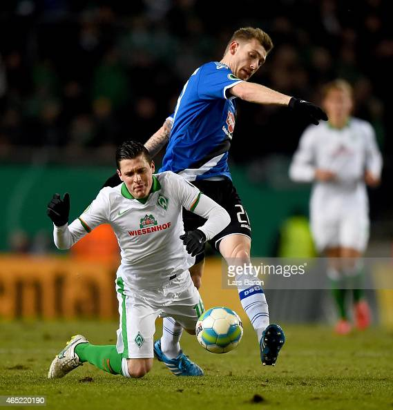 Zlatko Junuzovic of Werder Bremen is challenged by Manuel Junglas of Arminia Bielefeld during the round of 16 DFB Cup match between Arminia Bielefeld...