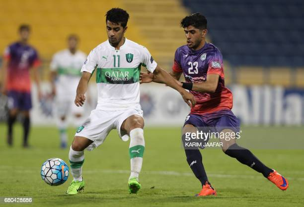 Zob Ahan's Danial Esmaeilifar fights for the ball with alAhli's Hussain Al Mogahwi during their Asian Champions League football match between Iran's...