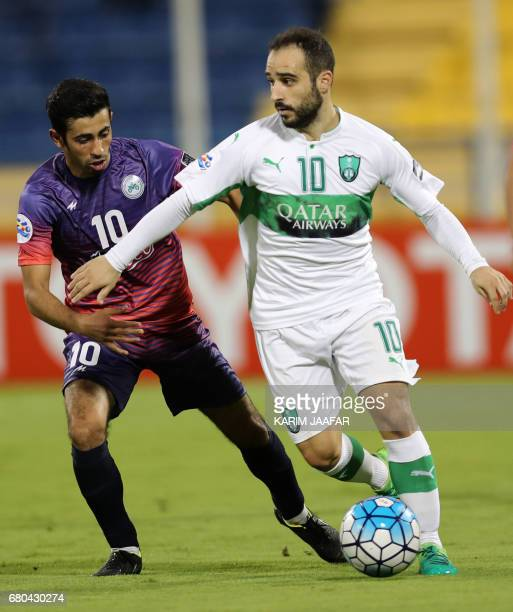 Zob Ahan's Ehsan Pahlevan fights for the ball with alAhli's Ioannis Fetfatzidis during their Asian Champions League football match between Iran's Zob...